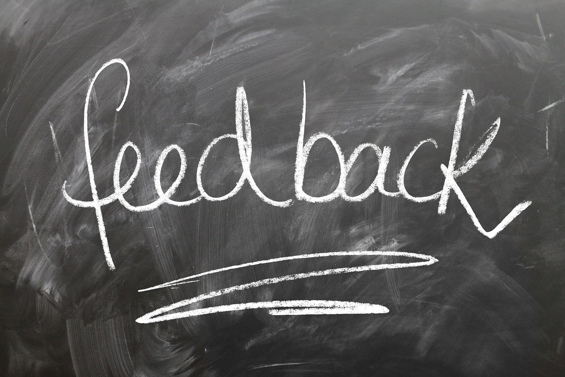 Musta liitutaulu, jossa lukee feedback.