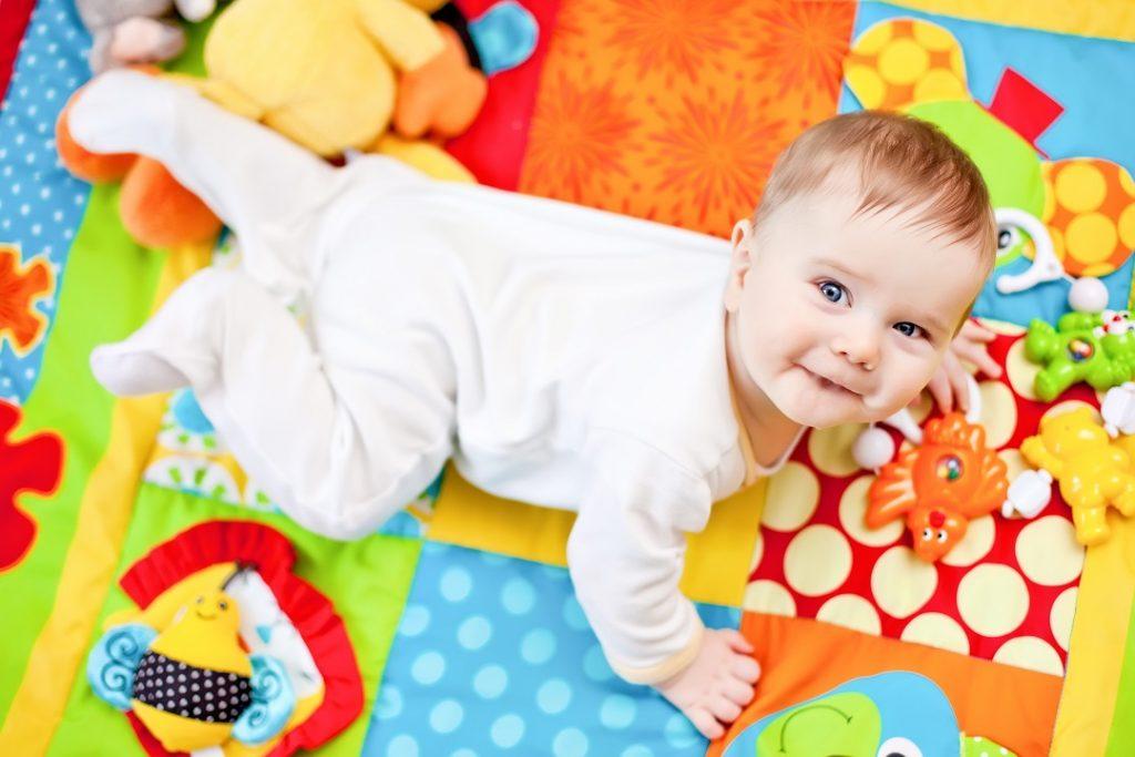 Pieni vauva leikkii värikkään leikkimaton päällä ja hymyilee.
