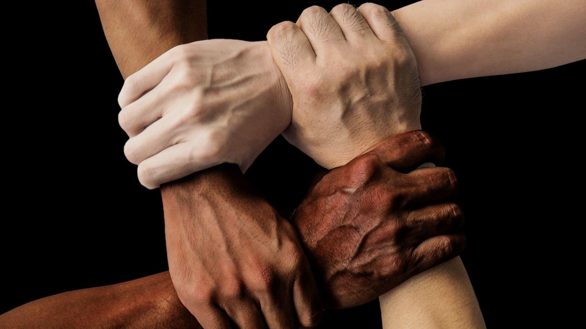 Käsiä, jotka pitävät kiinni toisten ranteista.