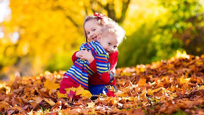 kaksi lasta halaa syksyn lehtien keskellä.