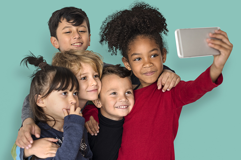 Children are taking a group selfie.