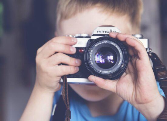 Lähikuva pojasta, joka kuvaa vanhalla järjestelmäkameralla.